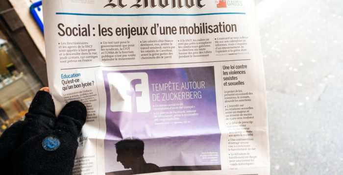 Man reading buying Le Monde newspaper at press kiosk featuring Mark Zuckerberg, Facebook CEO - scandat data leaks from Cambridge Analytica