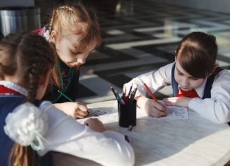 Schoolchildren draw with colored pencils sitting at the table
