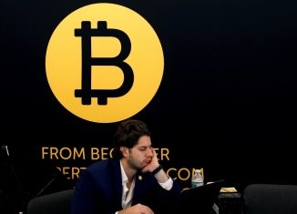 A man works on a laptop beneath the Bitcoin logo at the Consensus 2018 blockchain technology conference in New York City